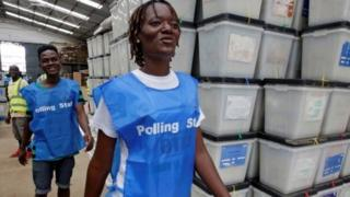 lection workers dey waka pass ballot boxes and voting materials for National Electoral Commission headquarters wey dey Monrovia, Liberia