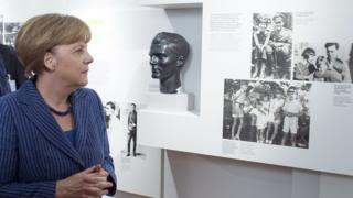 German Chancellor Angela Merkel stands next to a photo of anti-Nazi conspirator Claus von Stauffenberg while looking at exhibits at the newly-expanded museum of the German Resistance Memorial Center