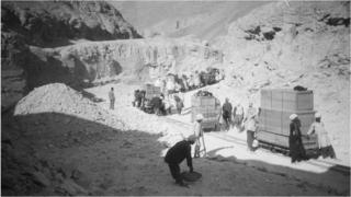 Team of archaeologists and assistants transporting crates on rails through rocky hills