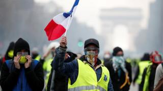 """Masked protesters wearing yellow vests, a symbol of a French drivers"""" protest against higher fuel prices, take part in a demonstration on the Champs-Elysees in Paris, France, November 24, 2018."""