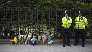 Police personnel stand beside floral tributes left in London's Russell Square on August 4, 2016, following an overnight stabbing spree that left one woman dead and five others injured.