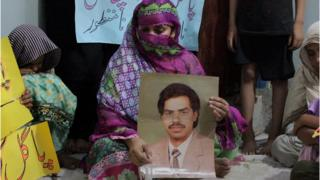 Safia Bano displays the picture of her husband Imdad Ali, a death row prisoner, while she sits with other family members in Burewala, in central Pakistan, Sunday, Sept. 18, 2016.