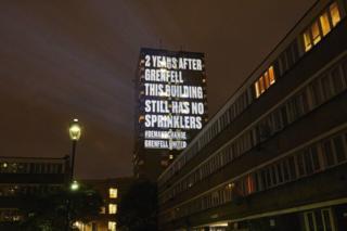 در دو سالگی آتش سوزی ساختمان گرنفل، پیامی با مضمون اینکه هنوز بعد از دو سال این ساختمان مجهز به آبپاش مخصوص آتشنشانی نیست بر روی ساختمانهایی در لندن و نیوکسل انداخته شده
