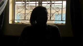 Woman in Kenya silhouetted against window