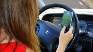 A person driving a car while holding a mobile phone