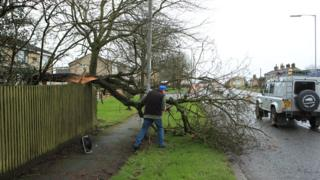 A man works to remove a tree blown over by Storm Dennis in Birkenshaw on the outskirts of Bradford