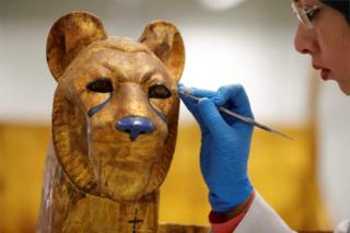 A gloved specialist uses an implement to restore the surface of a golden cat-like figure.