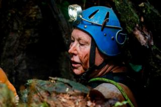 British cave-diver Robert Charles Harper explores an opening in the mountain during the rescue operation