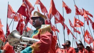 Hindistan Bengaluru'da işçiler geleneksel işçi bayramı kutlamalarında kırmızı uniformalarının içinde