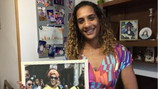 Anielle Silva holds up a photo of her sister Marielle Franco