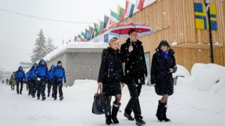 People walk through the resort town of Davos as snow falls ahead of the World Economic Forum (WEF) 2018 annual meeting, on January 22, 2018 in Davos