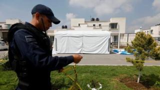 Un policía mira la carpa donde ocurrió una masacre.