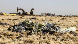 A power shovel digs next to debris at the crash site of Ethiopia Airlines plane