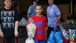 Dois meninos olham para foto, em área de banco de alimentos