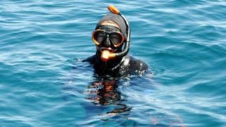 A woman in scuba gear floats in the water