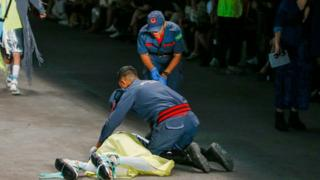 Paramedics attend to Tales Soares, who collapsed on the catwalk at Sao Paulo Fashion Week. He was later confirmed to have died