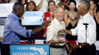 باراک اوباما برای کمک به اندرو گیلم (چپ) نامزد دموکراتها برای فرمانداری فلوریدا و همچنین کمک به سناتور دموکرات بیل نسلون (وسط) برای حفظ کرسی خود در سنا به فلوریدا رفت