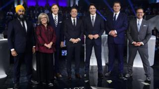 Canada's main party leaders pose before the final debate along with moderator Patrick Roy