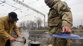 Ukrainian nationalist protesters and military veterans cook as they take part in a blockade against ongoing trade with Russian-backed insurgents, on February 23, 2017, in Kryvyi Torets railway station, Donetsk region