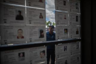 Don Pancho is seen looking through the notices of missing people