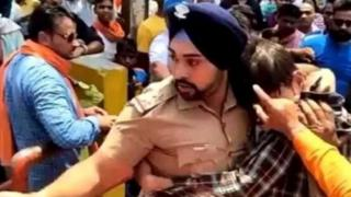 A Sikh police officer clung to a man amid a mob