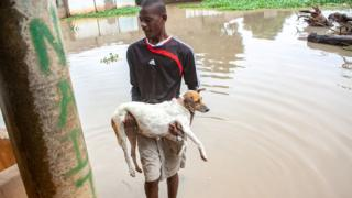 A man carries his dog in his arms through flood waters in a neighbourhood in Angola's capital Luanda on 10 January 2020