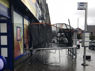 A trampoline stuck between a shop and a bus stop.