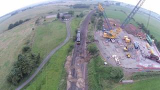 Shows the engine being lifted off the derailment site on Friday morning