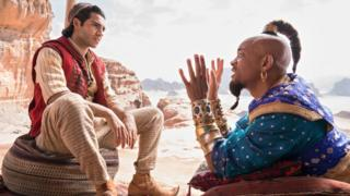 Aladdin and the Genie sit on the ground talking