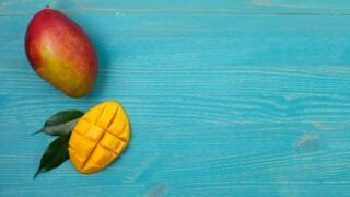 A whole mango and a half cut mango, on a blue wooden board