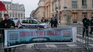 """Police stand by a banner reading """"End the state of emergency"""" during a demonstration on 5 Feb"""