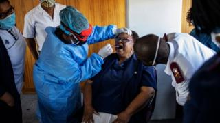 A doctor tests people for coronavirus in Johannesburg