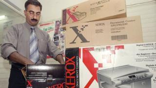 Un hombre desempaca un toner para fotocopiadoras Xerox.