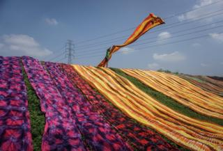 A worker throws out a brightly coloured cloth during a drying process.