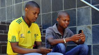 two south african men sitting on the steps using their mobile phones