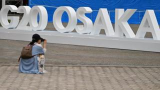 A woman takes a picture of a G20 Osaka design set up outside the venue for the G20 Osaka Summit in Osaka on June 26, 2019, ahead of the start of the summit later this week.