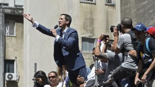 Venezuelan opposition leader and self declared acting president Juan Guaido speaks during a rally to press the military to let in US humanitarian aid, in eastern Caracas on February 12, 2019.