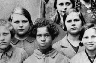 این دختر در میان همکلاسیهای سفیدپوستش که همگی به دوربین خیرهشدهاند، به شکلی رازآلود به سویی دیگر چشم دوخته است.