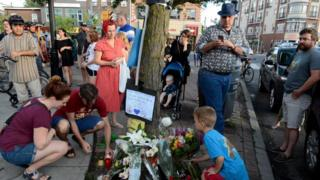Mourners leave flowers at a memorial for the victims of a mass shooting on Danforth Avenue in Toronto