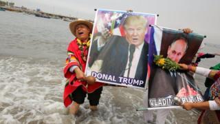 Перуанські шамани тримаючи портрети Дональда Трампа і Володимира Путіна під час ритуалу передбачень на наступний рік