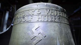 """Una campana de la época nazi, que tiene grabada una esvástica, una línea que dice """"Todo por la patria"""" y otra que dice """"Adolf Hitler""""."""