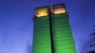 Grenfell Tower block lit up with green lights