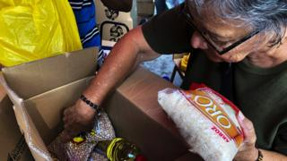 Woman inspects boxes of food from the state-run programme, Clap