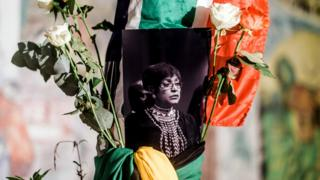 A black and white photograph of the late Winnie Madikizela-Mandela is surrounded by the South African and African National Congress (ANC) flags on a pole at the Old Durban Prison's Human Rights wall as South Africans gather to pay respect to the late high-profile anti-apartheid activist during a candle vigil in Durban on April 2, 2018.
