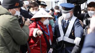 """Японские полицейские сопровождают пассажиров лайнера """"Даймонд принцесс"""""""