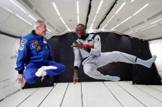 Usain Bolt and French astronaut Jean-Francois Clervoy float in the air in a plane