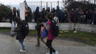Refugee girls look at local residents as they hold a protest outside a school at the Greek village of Profitis some 35 kilometers (22 miles) east of Thessaloniki, on Monday, Oct. 10, 2016