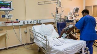 Nurse wey dey help patient for hospital room.