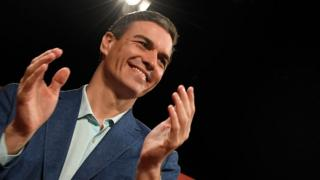 Pedro Sánchez claps against a black background, rimmed by light, in a photograph taken from below