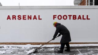 Staff work to clear clear Arsenal's training ground